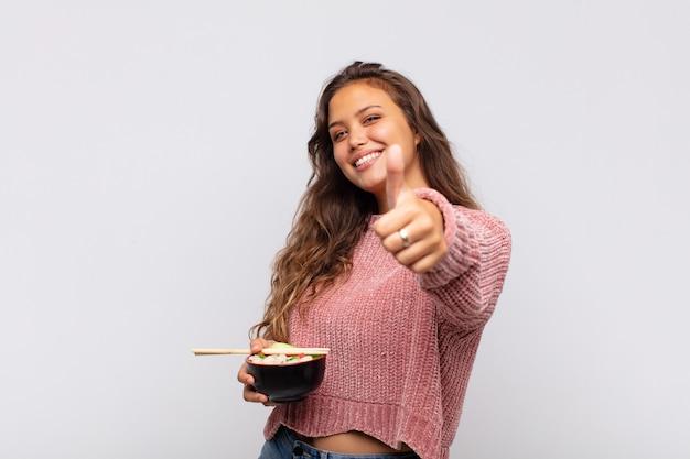 Mulher jovem e bonita com macarrão sentindo-se orgulhosa, despreocupada, confiante e feliz, sorrindo positivamente com o polegar para cima