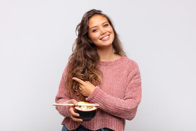 Mulher jovem e bonita com macarrão sorrindo alegremente, sentindo-se feliz e apontando para o lado e para cima, mostrando o objeto no espaço da cópia