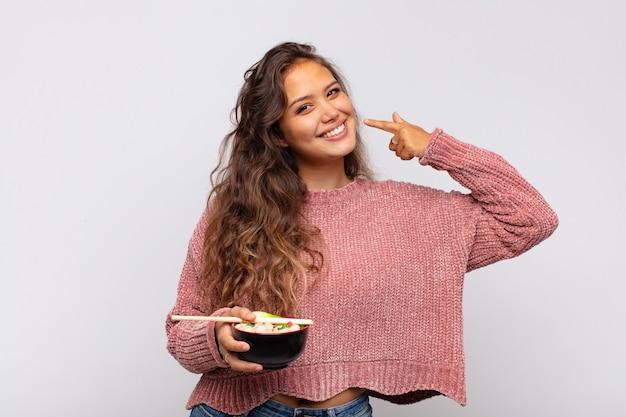 Mulher jovem e bonita com macarrão sorrindo com confiança apontando para o próprio sorriso largo, atitude positiva, relaxada e satisfeita