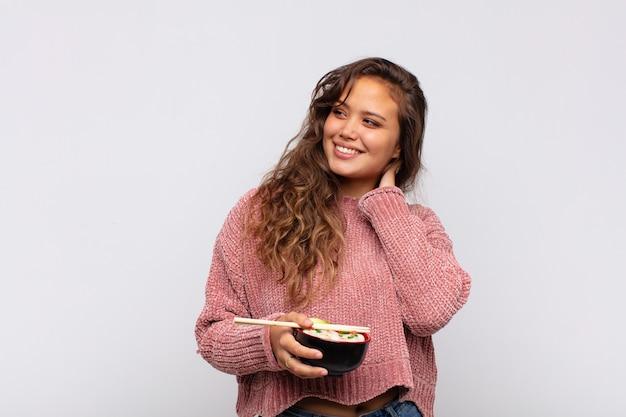 Mulher jovem e bonita com macarrão sorrindo com uma expressão feliz e confiante com a mão no queixo, pensando e olhando para o lado