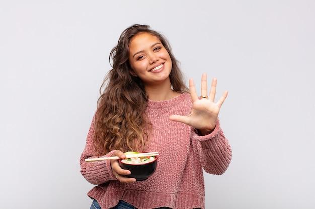 Mulher jovem e bonita com macarrão, sorrindo e parecendo amigável, mostrando o número cinco ou quinto com a mão para a frente, em contagem regressiva