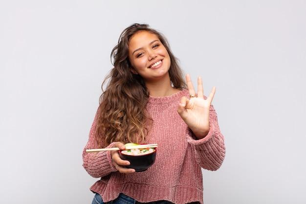 Mulher jovem e bonita com macarrão sorrindo e parecendo amigável, mostrando o número três ou o terceiro com a mão para a frente, em contagem regressiva