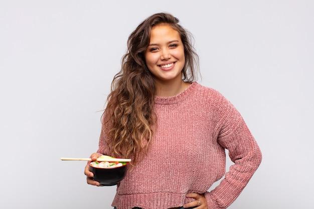 Mulher jovem e bonita com macarrão sorrindo feliz com uma mão no quadril e atitude confiante, positiva, orgulhosa e amigável