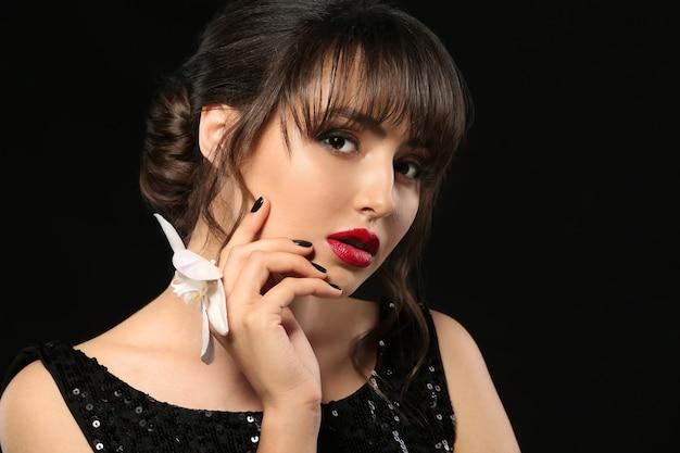 Mulher jovem e bonita com manicure profissional e flor