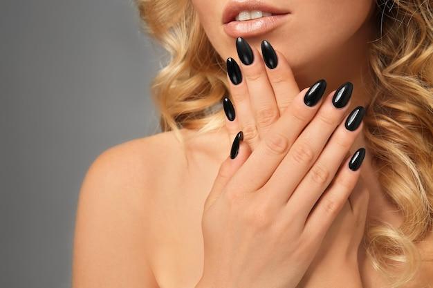 Mulher jovem e bonita com manicure profissional em cinza, close-up