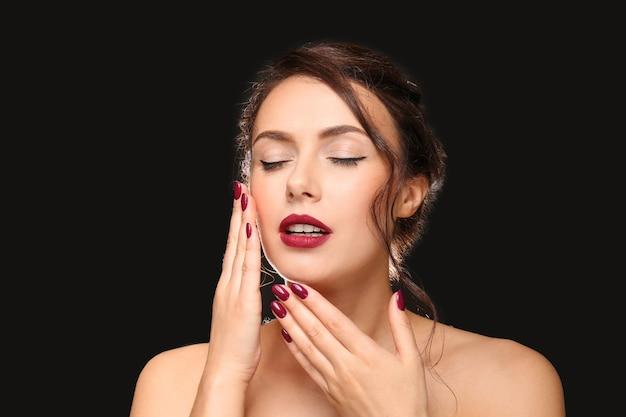 Mulher jovem e bonita com manicure profissional em fundo escuro