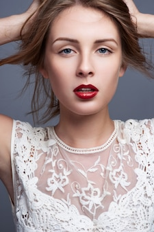 Mulher jovem e bonita com maquiagem brilhante, cara limpa, lábios vermelhos