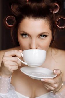 Mulher jovem e bonita com maquiagem, cacheados vestidos de branco e relaxando em casa, garota segurando uma xícara branca de café ou chá bebendo