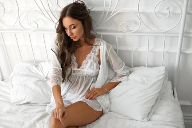 Mulher jovem e bonita com maquiagem e penteado na cama