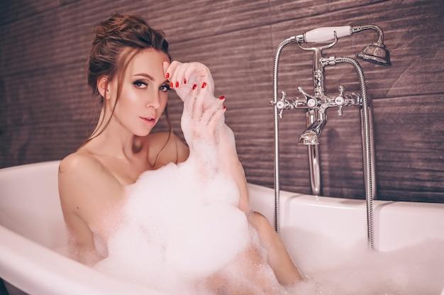 Mulher jovem e bonita com maquiagem e penteado relaxando tomando banho em uma banheira retrô cheia de espuma