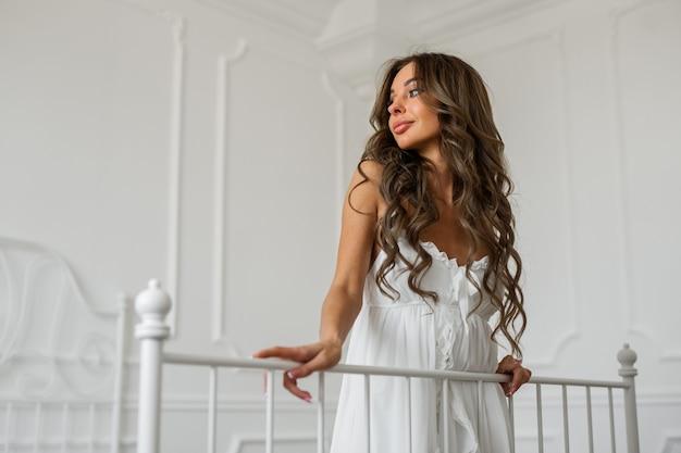Mulher jovem e bonita com maquiagem em vestido branco