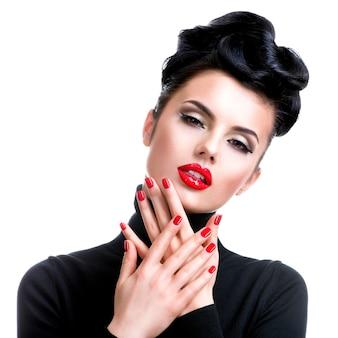 Mulher jovem e bonita com maquiagem profissional e manicure posando.