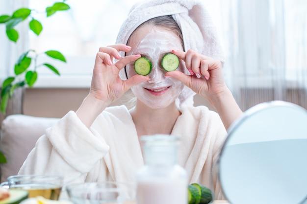 Mulher jovem e bonita com máscara cosmética natural e pepino no rosto. cuidados com a pele e tratamentos de spa em casa