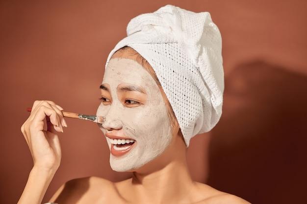 Mulher jovem e bonita com máscara de argila no rosto. cuidado da pele de salão, creme natural de algas.