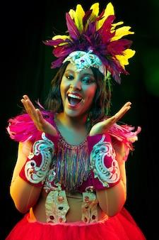 Mulher jovem e bonita com máscara de carnaval e fantasia de baile de máscaras com luzes coloridas