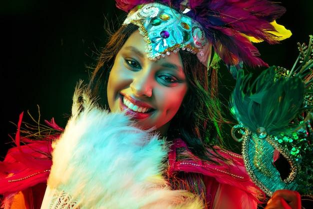 Mulher jovem e bonita com máscara de carnaval e fantasia elegante de baile de máscaras com leque de penas em luzes coloridas e brilho no fundo preto
