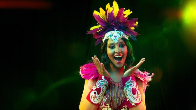 Mulher jovem e bonita com máscara de carnaval, elegante traje de baile de máscaras com penas e brilhos convidativos