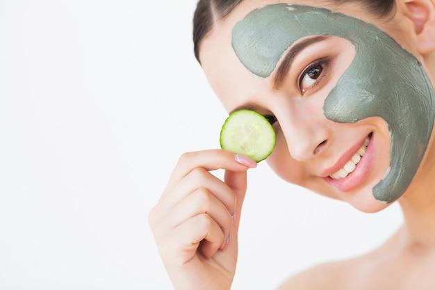 Mulher jovem e bonita com máscara de lama de argila no rosto, cobrindo os olhos com pepino fatia.
