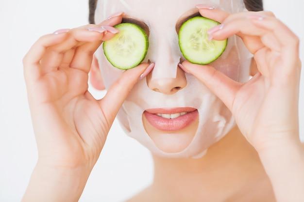 Mulher jovem e bonita com máscara de lama de argila no rosto cobrindo os olhos com pepino fatias,