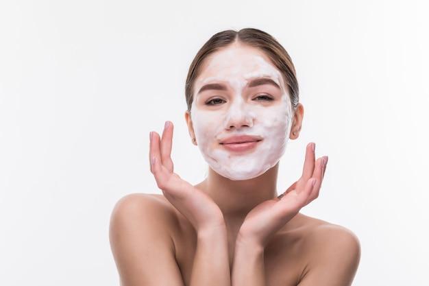 Mulher jovem e bonita com máscara facial na parede branca