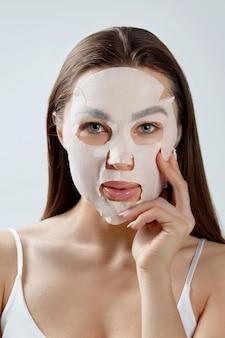 Mulher jovem e bonita com máscara facial olhando. procedimento cosmético. spa de beleza de menina e cosmetologia.
