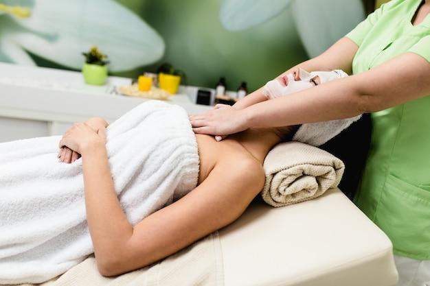 Mulher jovem e bonita com máscara facial, recebendo tratamento de massagem de spa no salão de beleza spa. tratamento de beleza facial.