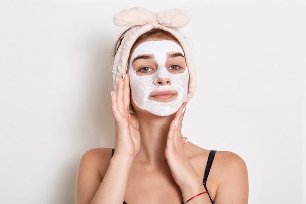 Mulher jovem e bonita com máscara facial, tratamento de beleza isolado, mantendo as palmas das mãos nas bochechas, parece confiante e satisfeita.