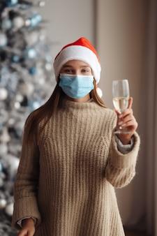 Mulher jovem e bonita com máscara protetora com taça de champanhe em casa