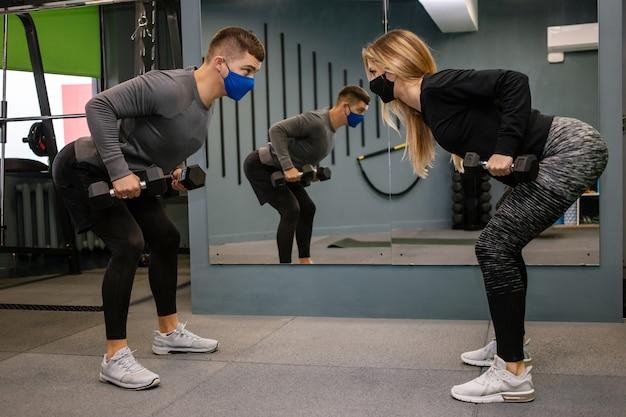 Mulher jovem e bonita com máscara protetora, malhando com o personal trainer na academia durante a pandemia de covid-19. esportista com máscara protetora.