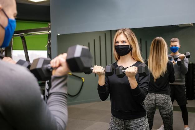 Mulher jovem e bonita com máscara protetora malhando com personal trainer na academia durante a pandemia de covid-19