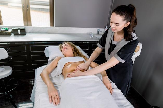 Mulher jovem e bonita com massagem na barriga no moderno centro médico e cosmetologia. terapeuta de massagem muito feminino massageando abdômen de mulher