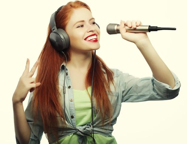 Mulher jovem e bonita com microfone e fones de ouvido em fundo cinza