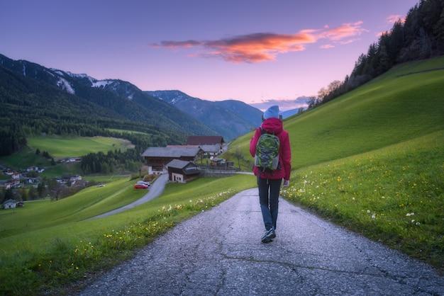 Mulher jovem e bonita com mochila está de pé na estrada da montanha ao pôr do sol no outono.