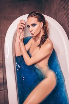 Mulher jovem e bonita com moda maquiagem, posando para tomar banho em uma banheira retrô cheia de água bomba cósmica azul colorida. conceito de spa e salão de beleza, cuidados com o corpo e a pele.