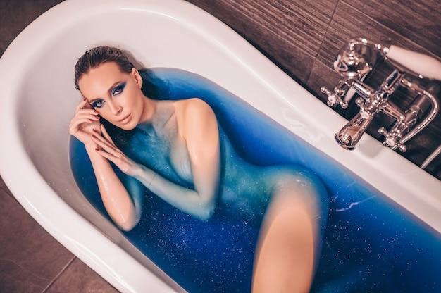 Mulher jovem e bonita com moda maquiagem, posando para tomar banho em uma banheira retrô cheia de água bomba cósmica azul colorida. conceito de spa e salão de beleza, cuidados com o corpo e a pele. Foto Premium