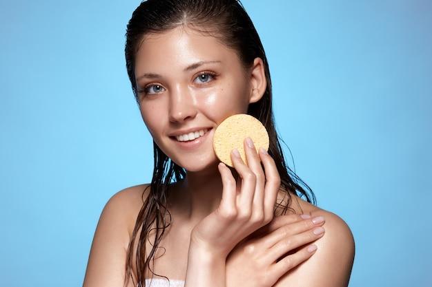 Mulher jovem e bonita com o cabelo molhado limpando o rosto com esponja