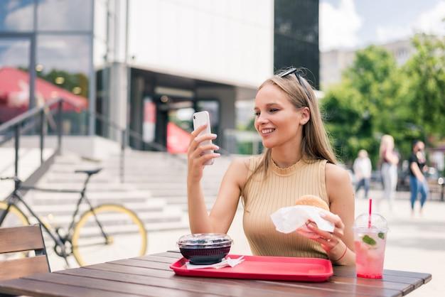 Mulher jovem e bonita com o celular, comendo hambúrguer saboroso em uma cafeteria ao ar livre
