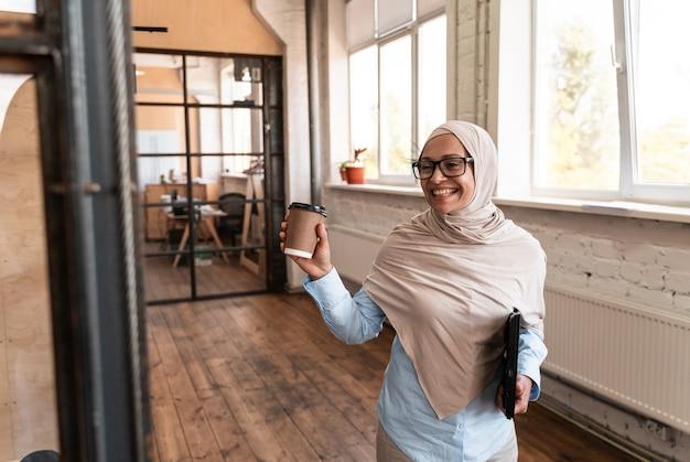 Mulher jovem e bonita com o hijab trabalhando no escritório