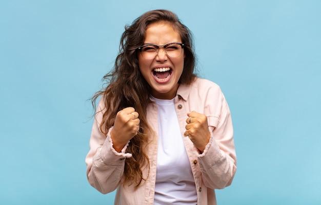 Mulher jovem e bonita com óculos e camisa aberta jeans posando na parede azul