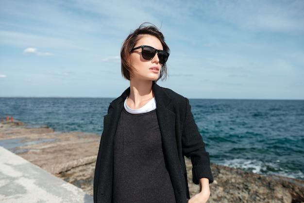 Mulher jovem e bonita com óculos escuros e jaqueta preta caminhando perto do mar