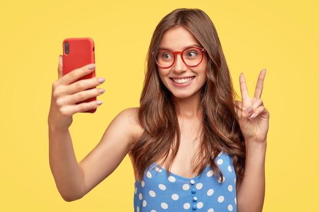 Mulher jovem e bonita com óculos posando contra a parede amarela