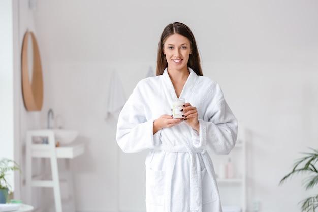 Mulher jovem e bonita com óleo de coco no banheiro