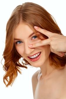 Mulher jovem e bonita com olhos azuis e lábios vermelhos mostra dois dedos.