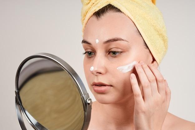 Mulher jovem e bonita com ombros nus, toalha amarela na cabeça, aplicação de creme no rosto, olhar no espelho, isolamento em uma parede cinza