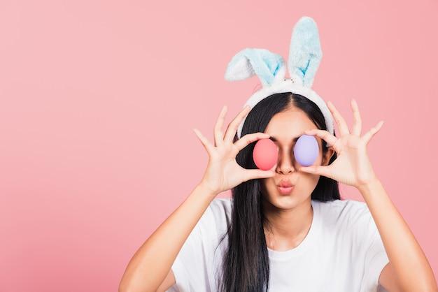 Mulher jovem e bonita com orelhas de coelho e olhos frontais de ovos de páscoa coloridos