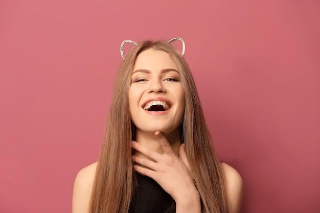 Mulher jovem e bonita com orelhas de gato rosa