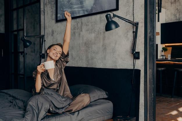 Mulher jovem e bonita com os olhos fechados e o cabelo preso em um coque começando de manhã com uma xícara de café quente, se espreguiçando na cama em casa enquanto está sentada com um pijama de cetim após acordar da noite de sono