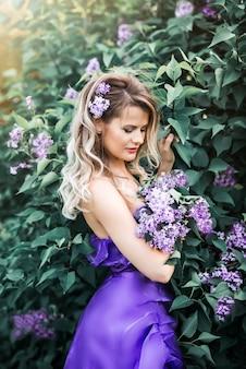 Mulher jovem e bonita com os olhos fechados, rodeado de lilás. flor de primavera.