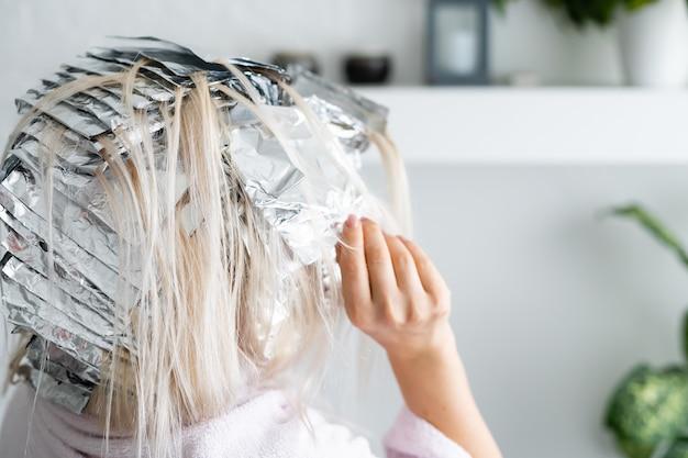 Mulher jovem e bonita com papel alumínio. processo de branqueamento ou tingimento em casa