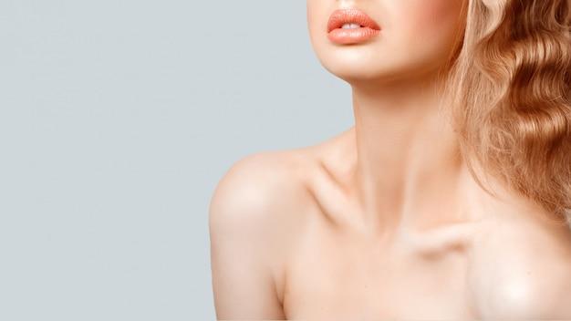 Mulher jovem e bonita com pele brilhante suave fresca e perfeitos lábios carnudos.